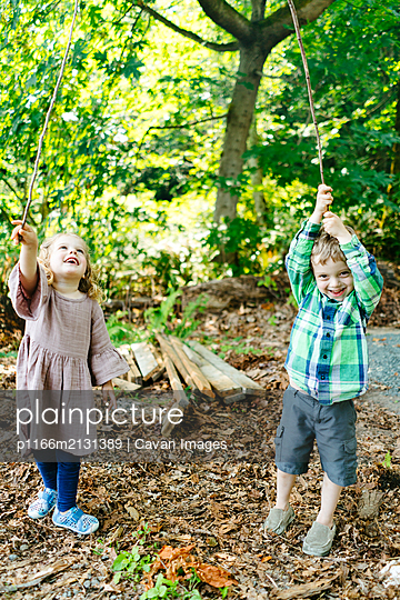 Straight on portrait of a girl and a boy playing in the forest - p1166m2131389 by Cavan Images