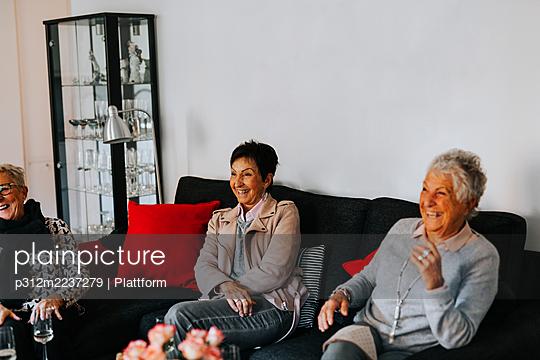 Happy senior friends sitting in living room - p312m2237279 by Plattform