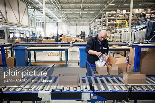 Male warehouse worker packing cardboard boxes for conveyer belt - p429m803052f by Arno Masse