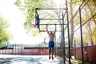 Determined athlete doing chin-up on basket ball hoop - p1166m1164489 by Cavan Images