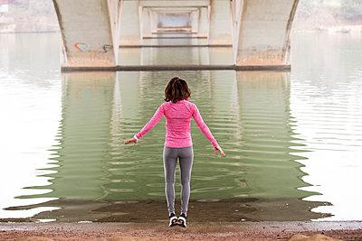 Rear view of woman jumping at lakeshore below Lamar Boulevard Bridge - p1166m1423118 by Cavan Images