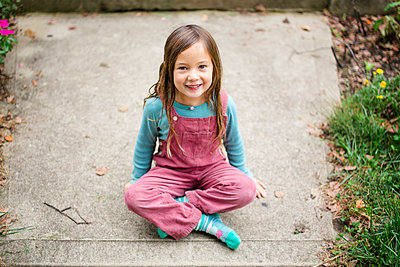 Portrait of a happy little girl sitting on the sidewalk smiling - p1166m2078470 by Cavan Images