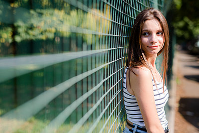 Portrait of smiling young woman standing at a fence - p300m2029100 by Giorgio Fochesato