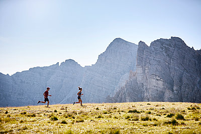 Man and woman running in the mountains - p300m2166297 von Christian Vorhofer