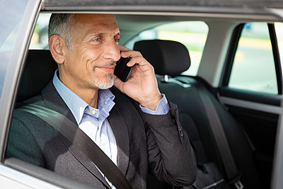 Smiling male professional talking on mobile phone in car - p300m2287634 by Emma Innocenti
