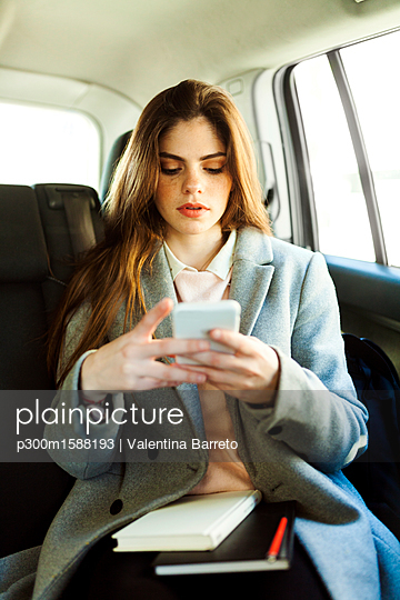 Portrait of young businesswoman sitting on backseat of a car looking at cell phone - p300m1588193 von Valentina Barreto
