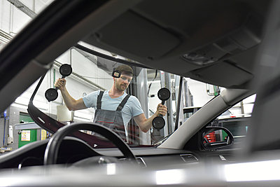Car mechanic in a workshop changing car window - p300m1450123 by lyzs