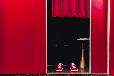 Man wearing red sneakers standing behind curtain in a photo booth - p300m2170871 by Francesco Morandini