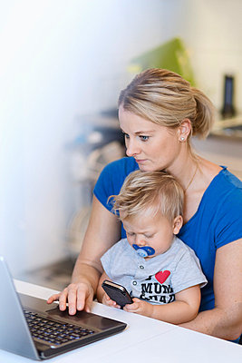 Mother working on laptop while baby using mobile phone at table - p426m1017817f by Maskot