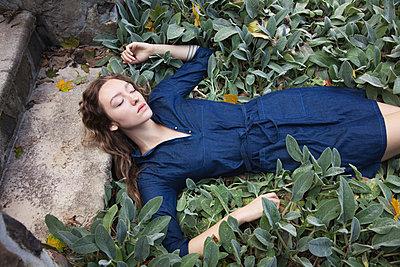 Woman sleeping in leafy garden - p555m1409420 by Shestock