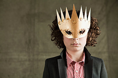 Young boy wearing gold crown mask - p9244312f by Image Source