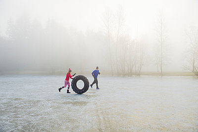 Woman rolling tyre on frozen lake - p924m1230211 by Pete Saloutos
