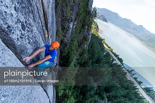 Man lead climbing granite Squamish with background view of ocean - p1166m2191916 by Cavan Images