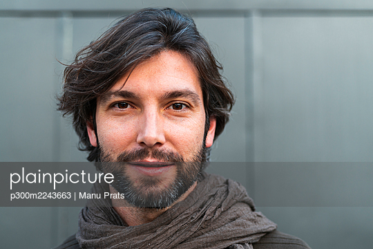 Portrait of man wearing scarf in front of gray wall - p300m2243663 by Manu Prats