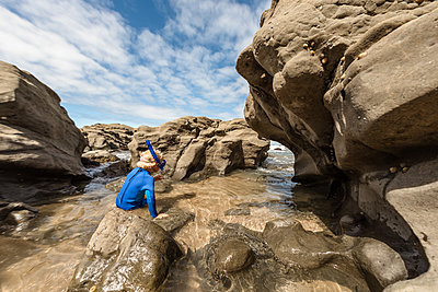 Young child preparing to snorkel at a rocky coast - p1166m2138199 by Cavan Images