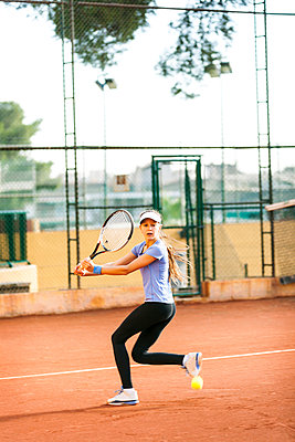 Teenage girl playing tennis on court - p300m1356584 by Valentina Barreto