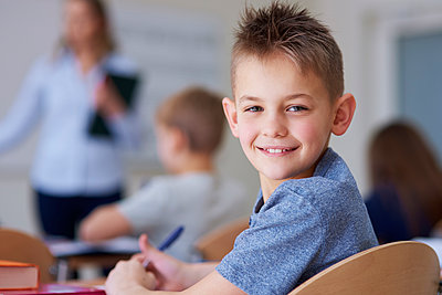 Portrait of smiling schoolboy in class - p300m1588099 by gpointstudio