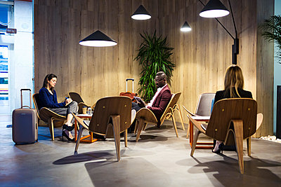 Business people sitting in hotel lobby, working - p300m2083437 by Josep Suria