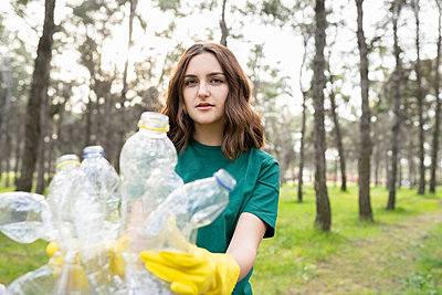 Young environmentalist collecting plastic bottles in forest - p300m2282168 by Jose Carlos Ichiro