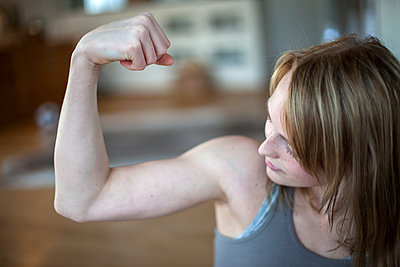 Young woman flexing muscles in gym - p312m1470550 by Christina Strehlow