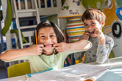 Hispanic children making faces together - p555m1454143 by Jon Feingersh
