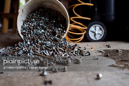 Close-up of nuts and bolts spilling from bucket at factory - p1166m1545554 by Cavan Social