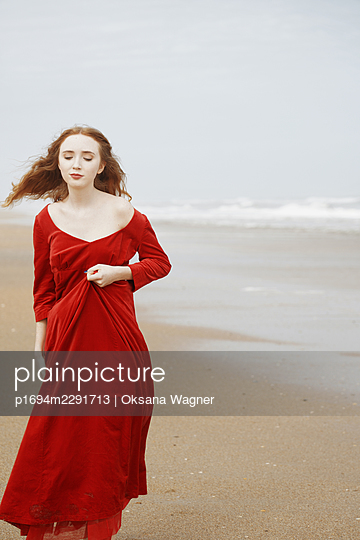 Beautiful young woman in red velvet dress walking in a hurry on the beach - p1694m2291713 by Oksana Wagner