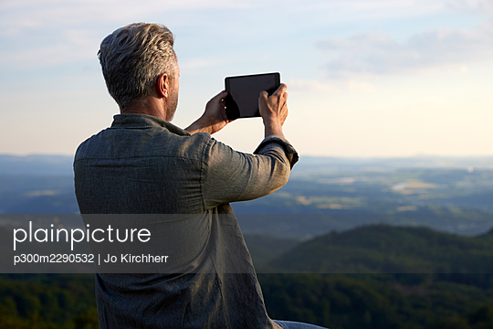 Male hiker photographing through digital tablet during sunset - p300m2290532 by Jo Kirchherr