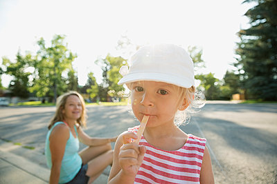 Portrait smiling girl eating flavored ice on sunny sidewalk - p1192m1184012 by Hero Images