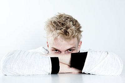 Junger Mann mit auf dem Tisch verschränkten Armen - p1195m1466342 von Kathrin Brunnhofer