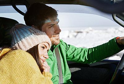 Happy couple driving car in winter landscape - p1577m2150278 by zhenikeyev