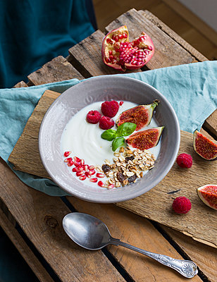 Bowl of natural yoghurt with fruit muesli, raspberries, figs and pomegranate seed - p300m2060460 by JLPfeifer