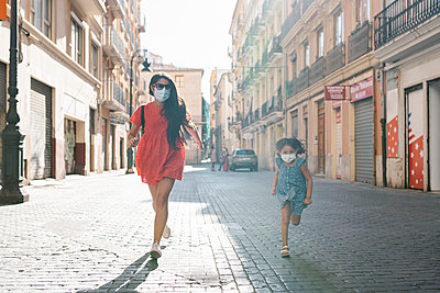 Cheerful mother and daughter wearing masks running on street in city - p300m2220679 by Ezequiel Giménez