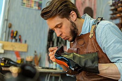 Male cobbler gluing shoe at workshop - p300m2282561 by Vladimir Godnik