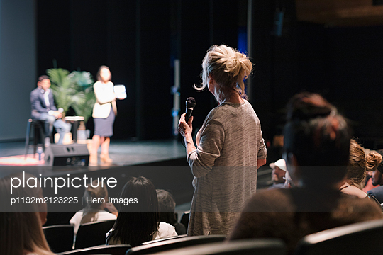 Woman in audience with microphone asking speakers a question - p1192m2123225 by Hero Images