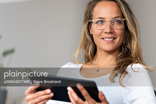 Smiling woman with eyeglasses looking away while holding digital tablet at home - p300m2277495 by Steve Brookland