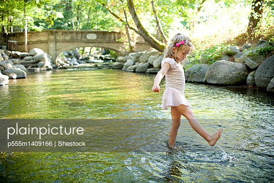Girl splashing in park river - p555m1409166 by Shestock
