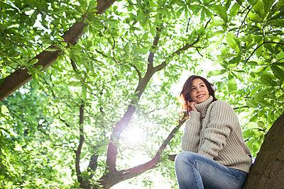 Frau sitzt glücklich auf einem Baum - p045m2021914 von Jasmin Sander