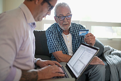Son helping senior father with credit card paying bills online - p1192m1529729 by Hero Images