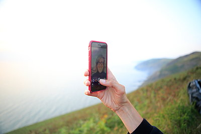 Woman on the waterfront takes a selfie - p179m1467577 by Roland Schneider