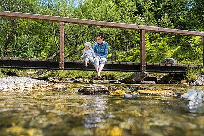 Mother and daughter sitting on wooden bridge, mountain stream - p300m2023542 von Daniel Ingold