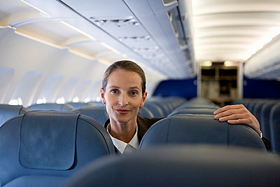 A woman looking over the top of airplane seats - p3018321f by Halfdark
