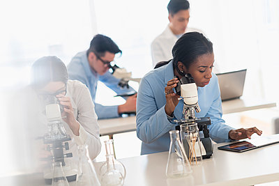 Scientists using microscopes and digital tablet in research laboratory - p555m1413004 by JGI/Tom Grill
