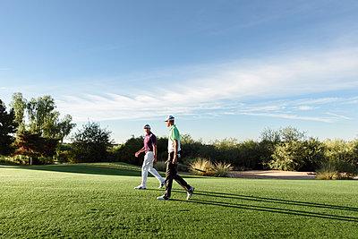Friends walking on golf course - p555m1472897 by Kolostock