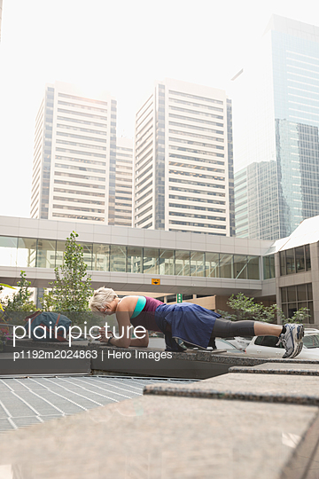 Athletic mature female runner exercising, in plank position in city