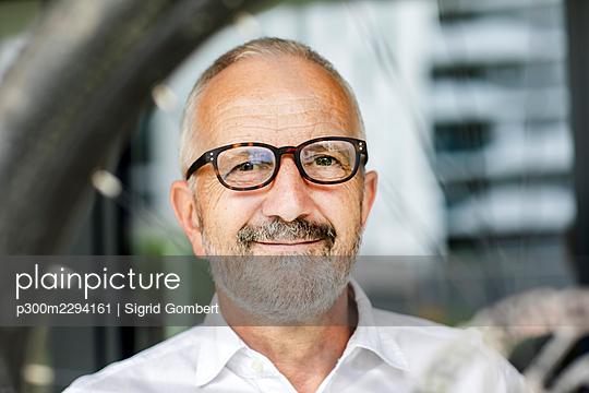 Smiling businessman wearing eyeglasses - p300m2294161 by Sigrid Gombert