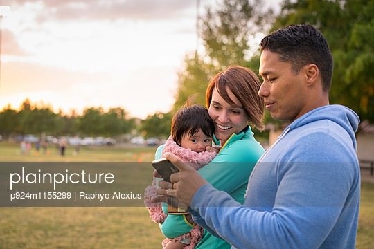 Couple with baby, using mobile phone in park - p924m1155299 by Raphye Alexius