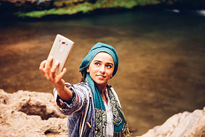 High angle view of woman taking selfie through mobile phone while standing at riverbank - p1166m1416180 by Cavan Images