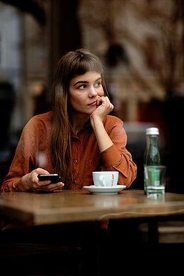 Junge Frau im Cafe schaut aus dem Fenster - p1212m1084157 von harry + lidy