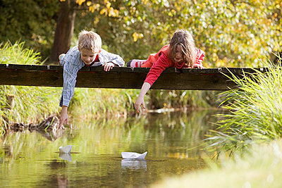 Boy (10-13) and girl (7-9) lying on bridge watching paper boats in water - p3006184f by Rainer Dittrich